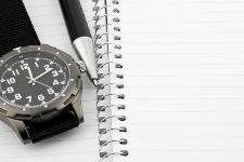 Pen and watch on notebook with room for text